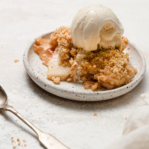 apple crisp on white plate with ice cream