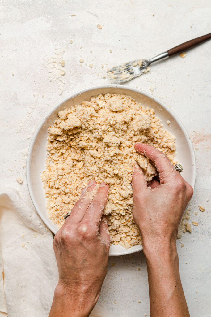 mixing crumble with hands