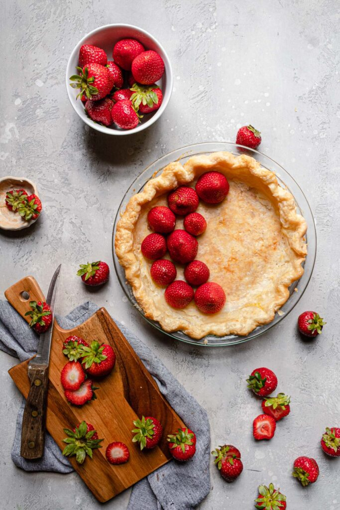 putting strawberries into pie crust