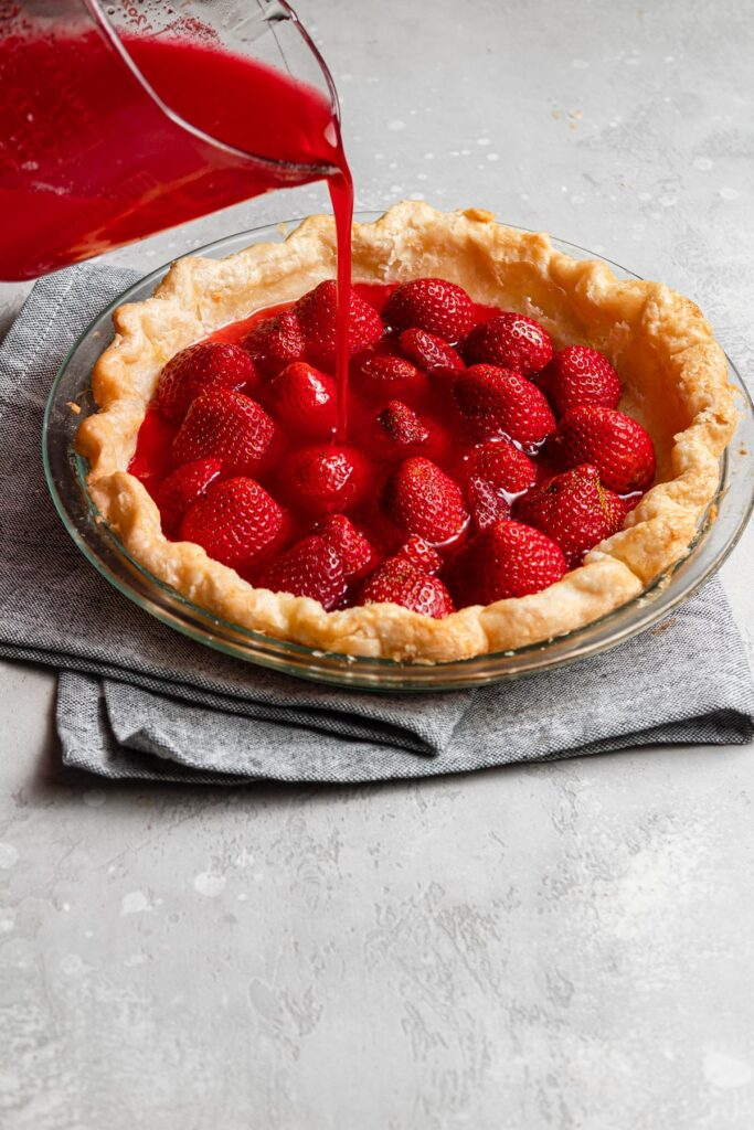 pouring jello over strawberries in pie shell