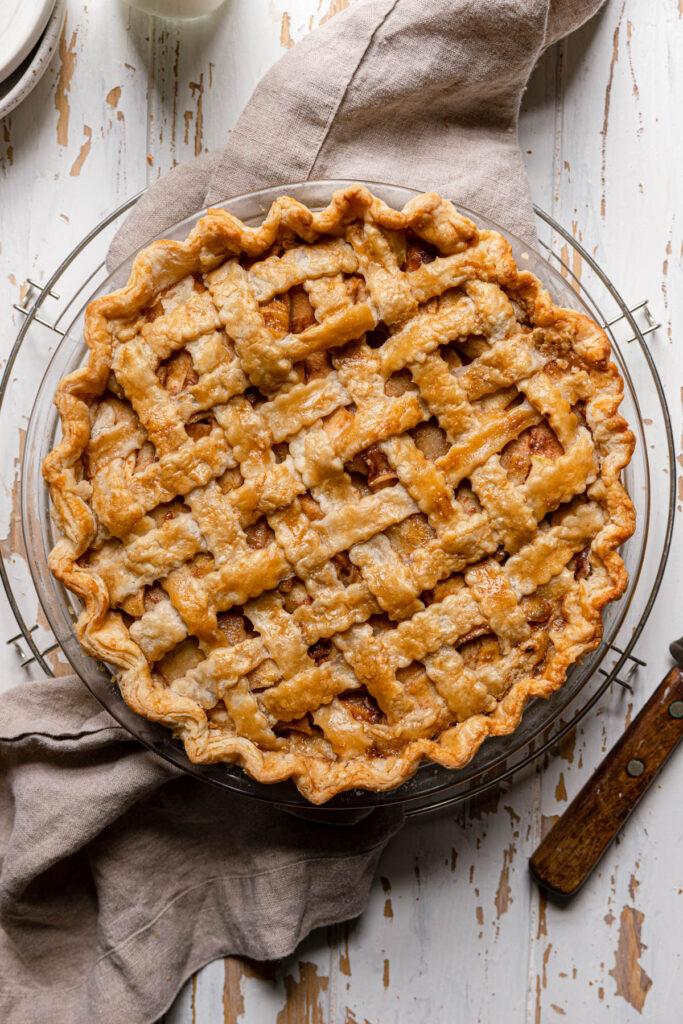 overhead shot of baked apple pie with lattice crust on grey napkin