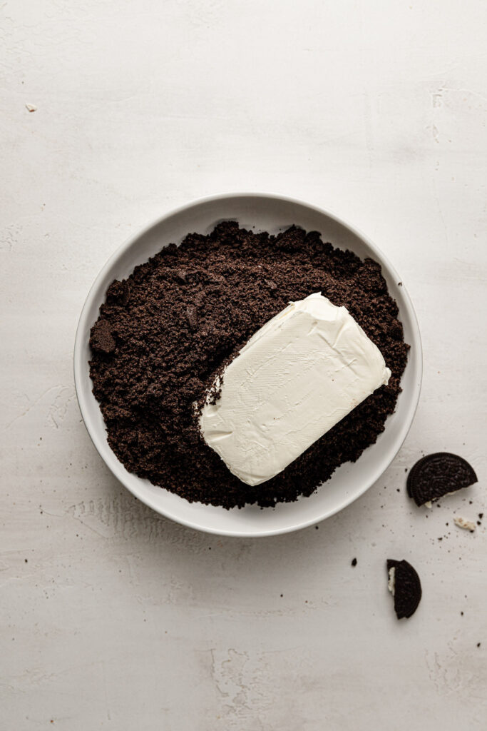 oreo crumbs and cream cheese in bowl