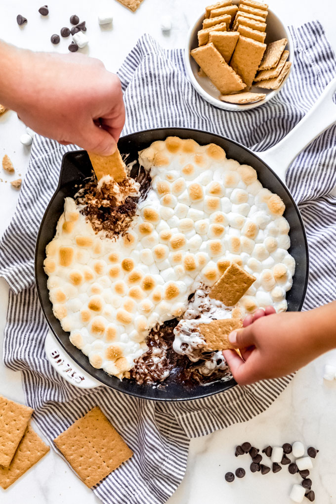 Two hands holding graham crackers to scoop melted s'mores dip from a skillet.