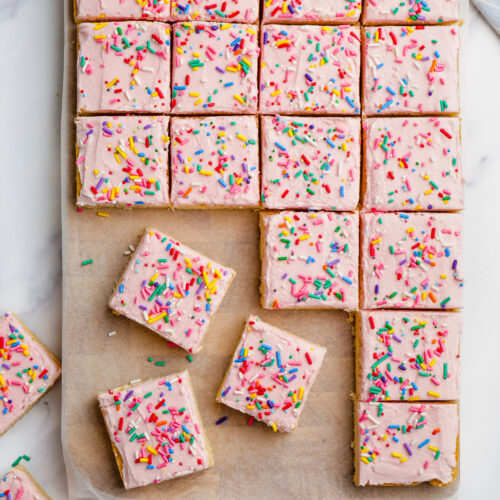 sugar cookie bars with pink frosting and sprinkles cut into bars