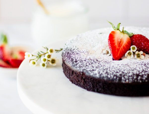 whole flourless chocolate cake on cake stand
