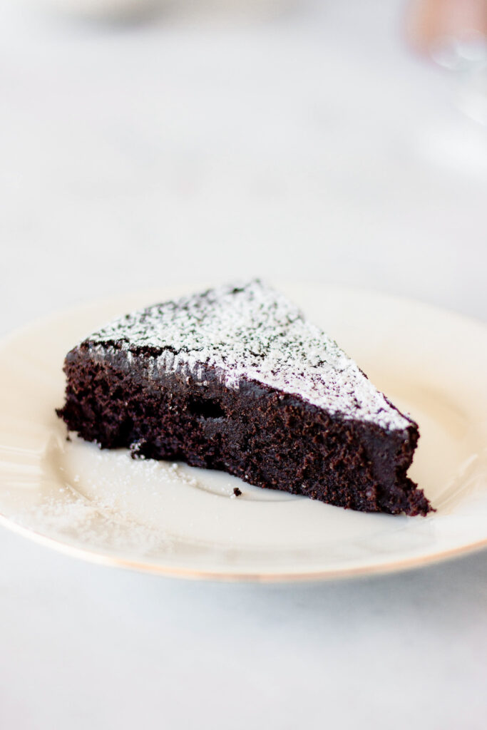 slice of flourless chocolate cake with powdered sugar