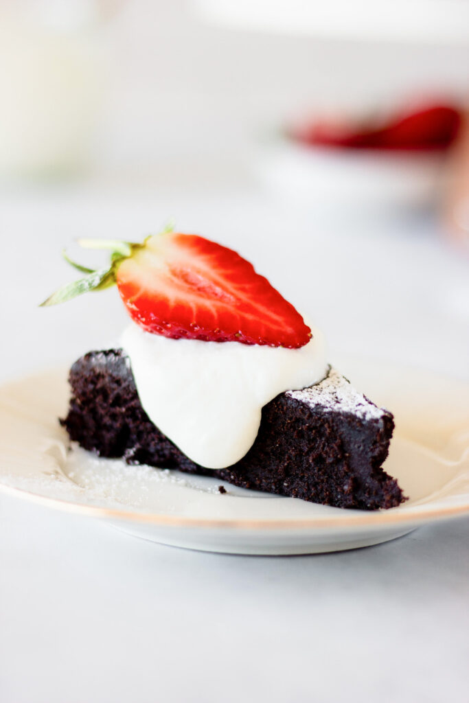 slice of flourless chocolate cake with cream and strawberry