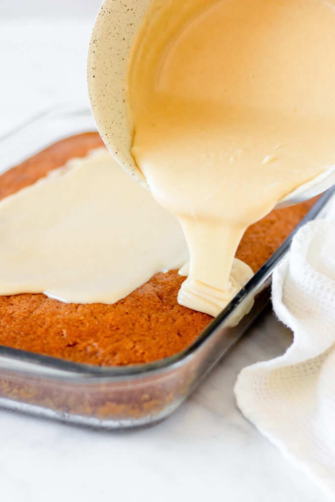pouring brown butter icing overtop cake