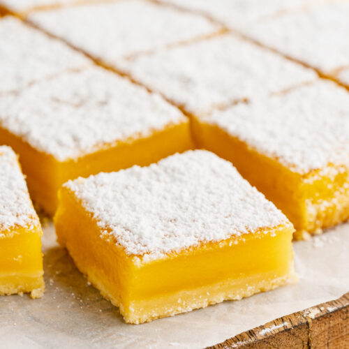 lemon bars on a parchment paper lined cutting board