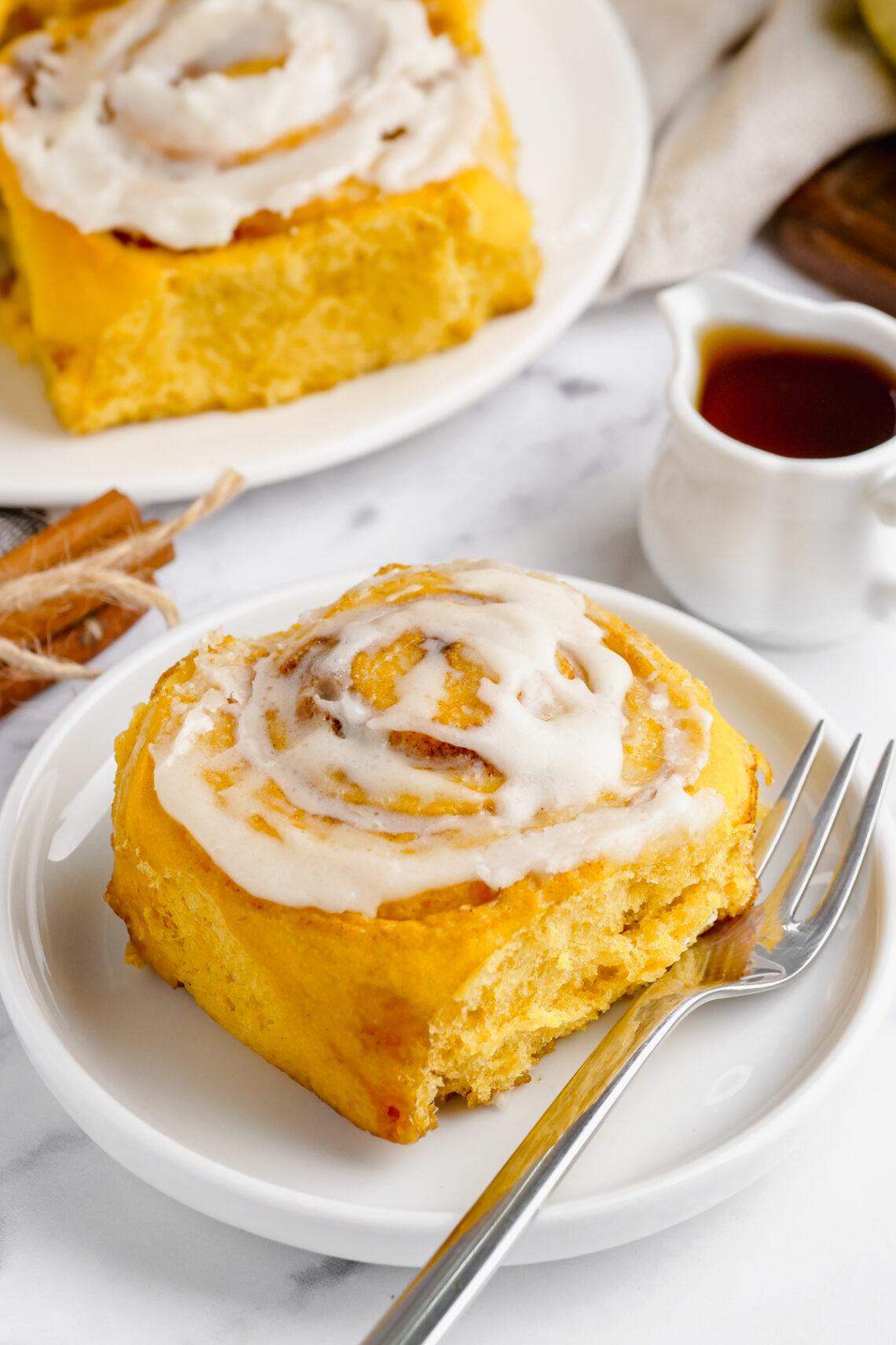 pumpkin cinnamon roll on a white plate