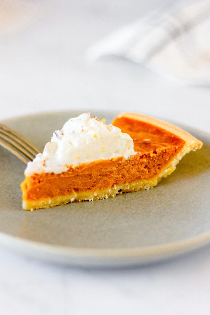 slice of pumpkin pie on grey plate