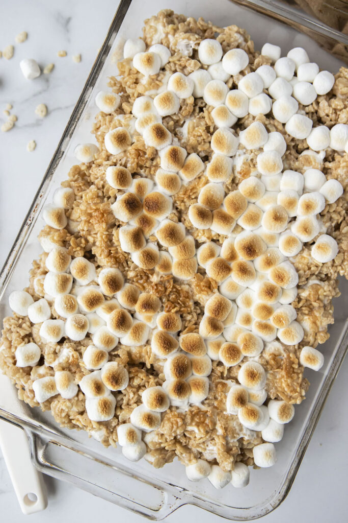 toasted marshmallows on top of brown butter rice krispie treats