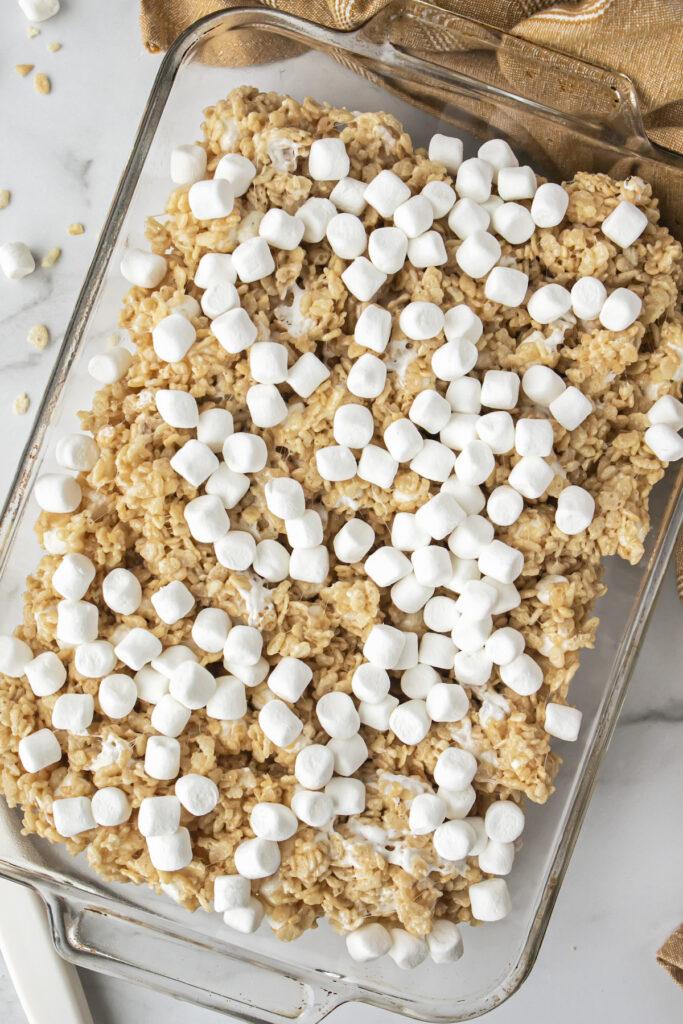 untoasted marshmallows on top of brown butter rice krispie treats