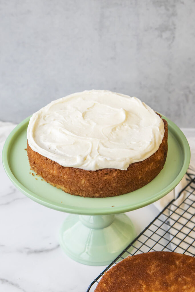 baked coconut cake with cream cheese frosting on top of it