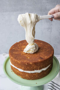 cream cheese falling from spatula onto second layer of coconut cake