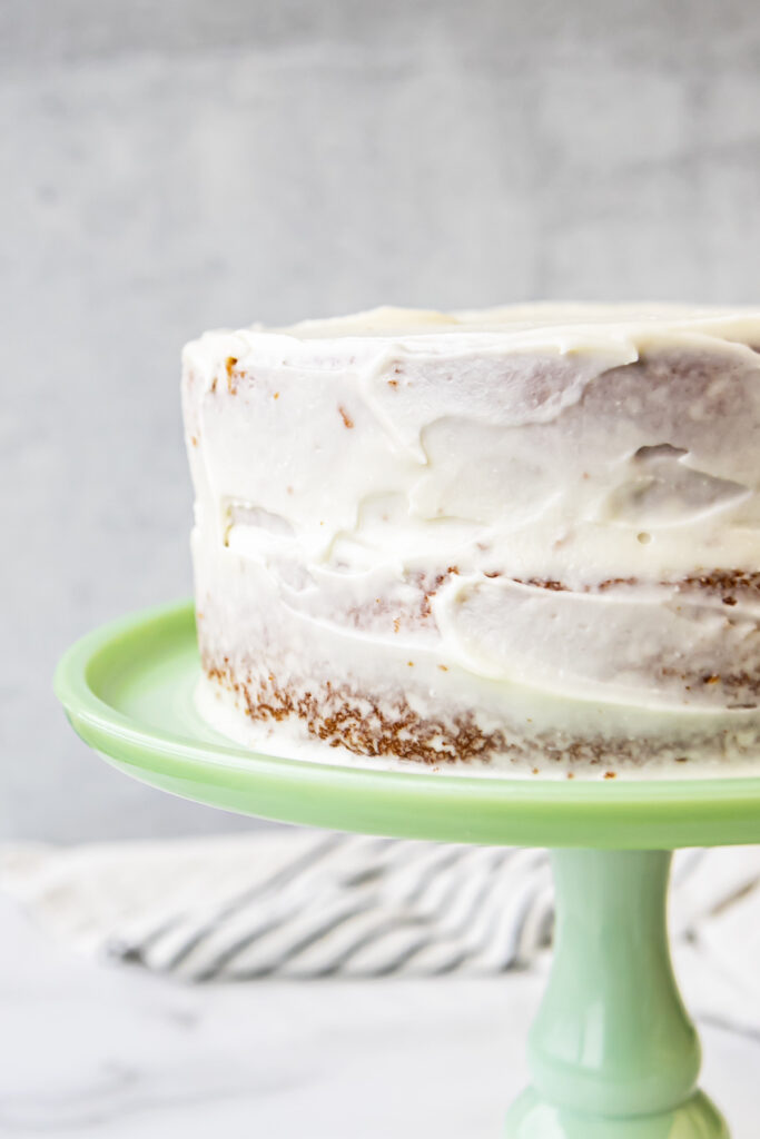 roughly frosted coconut cake on a bright green cake stand