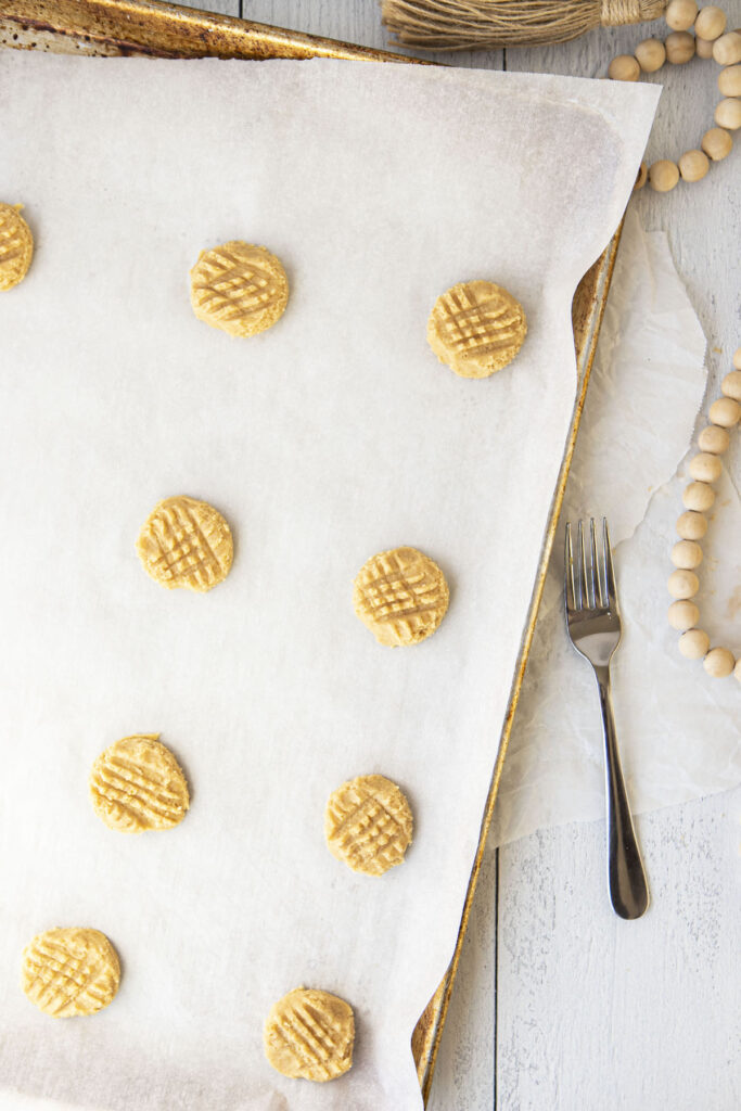 peanut butter cookie dough balls squished down with a fork on a parchment paper lined baking sheet