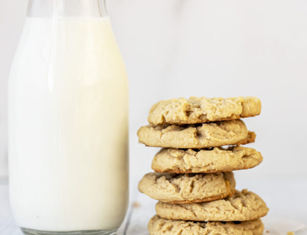 peanut butter cookies stacked on top of each other next to a glass of milk