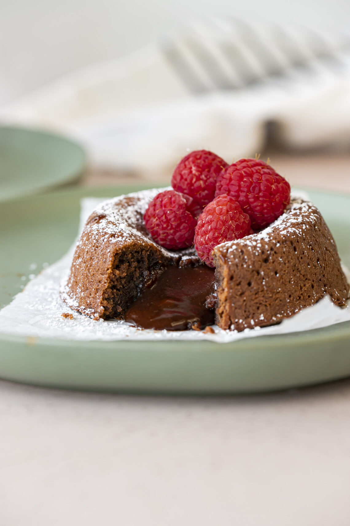 lava cake cut open with powdered sugar and raspberries on top