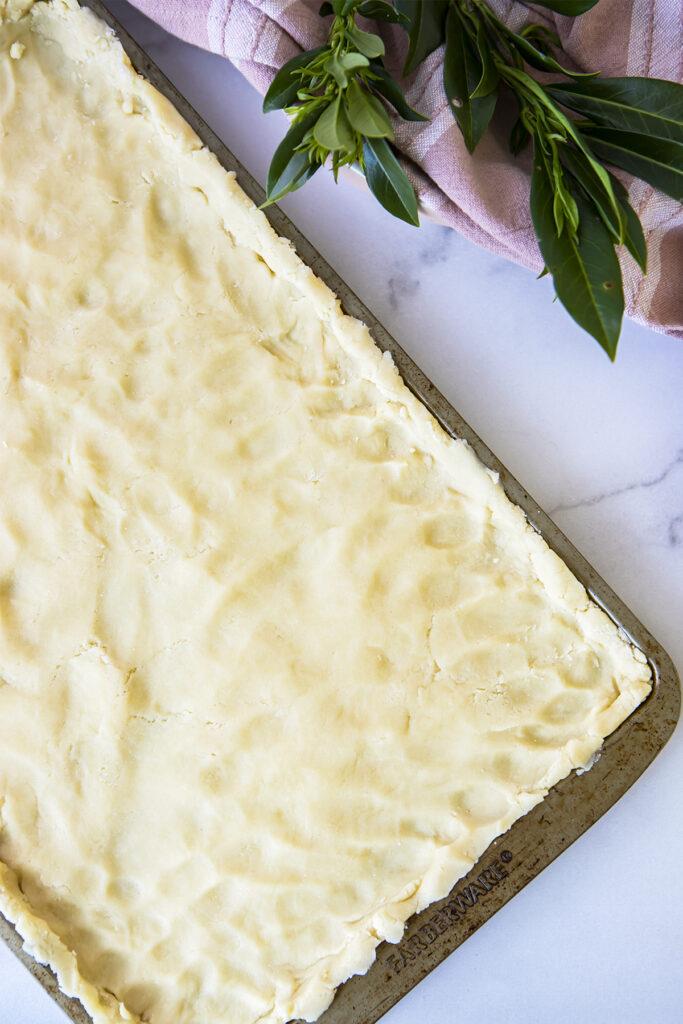 sugar cookie dough smooshed into a baking sheet