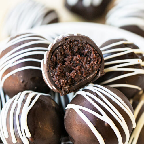 chocolate cake balls stacked on top of each other, one has a bite taken out of it