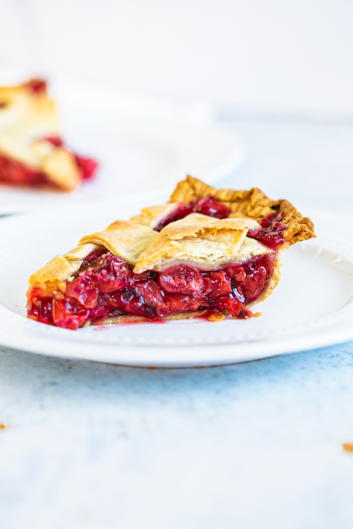 side view of baked cherry pie slice on a plate