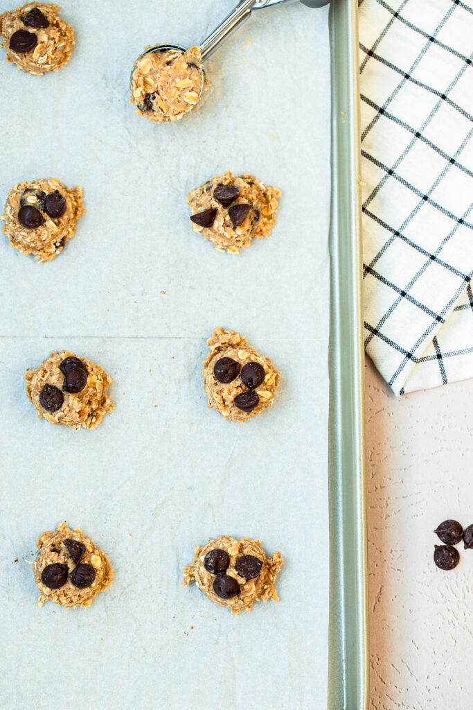 oatmeal chocolate chip cookie dough balls on a parchment paper lined baking sheet