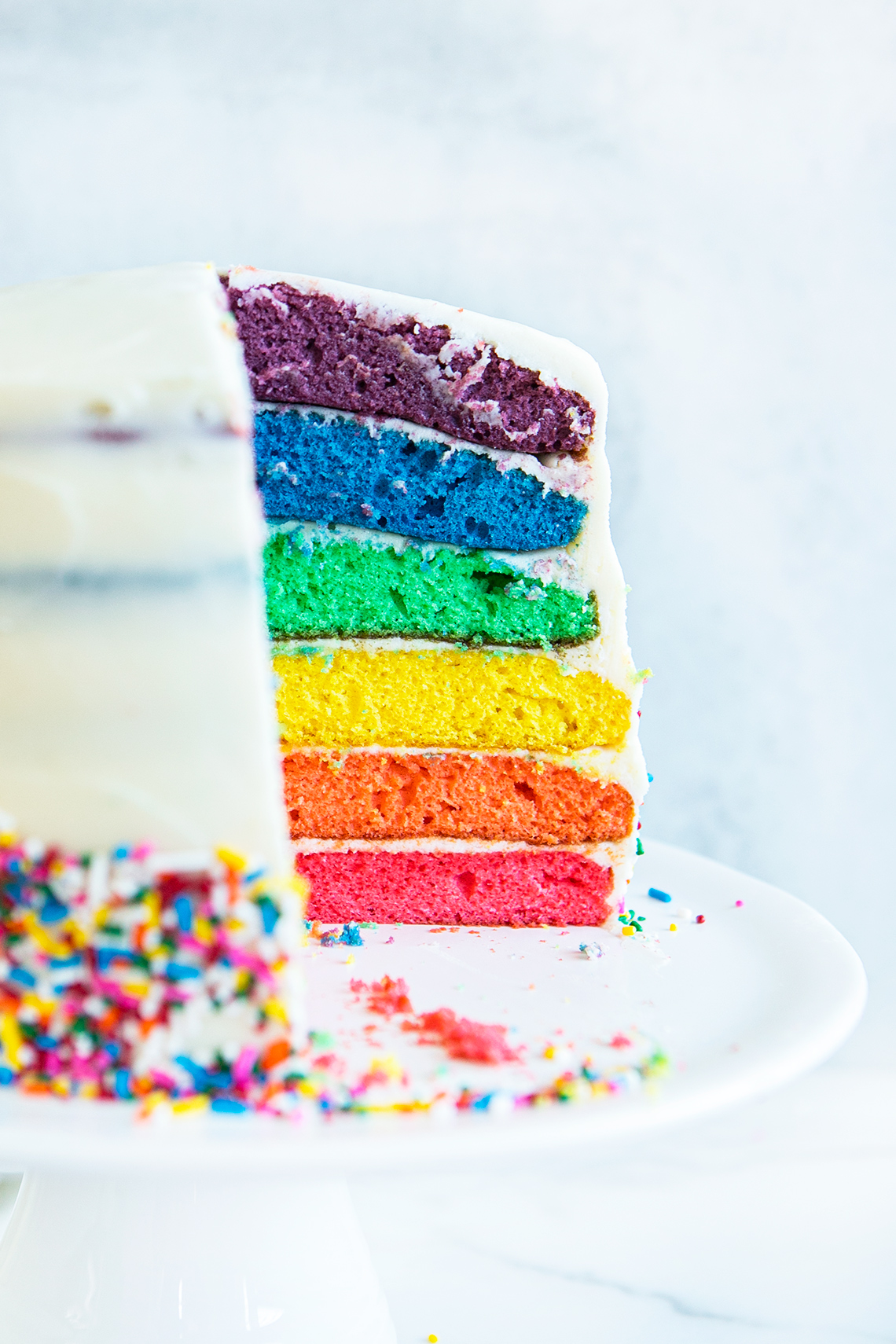 side view of rainbow cake with a slice cut out