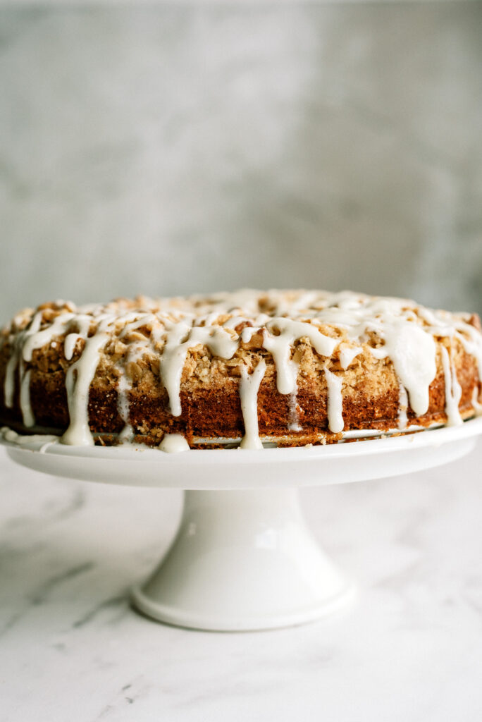 apple crumble cake with icing all on a cake stand