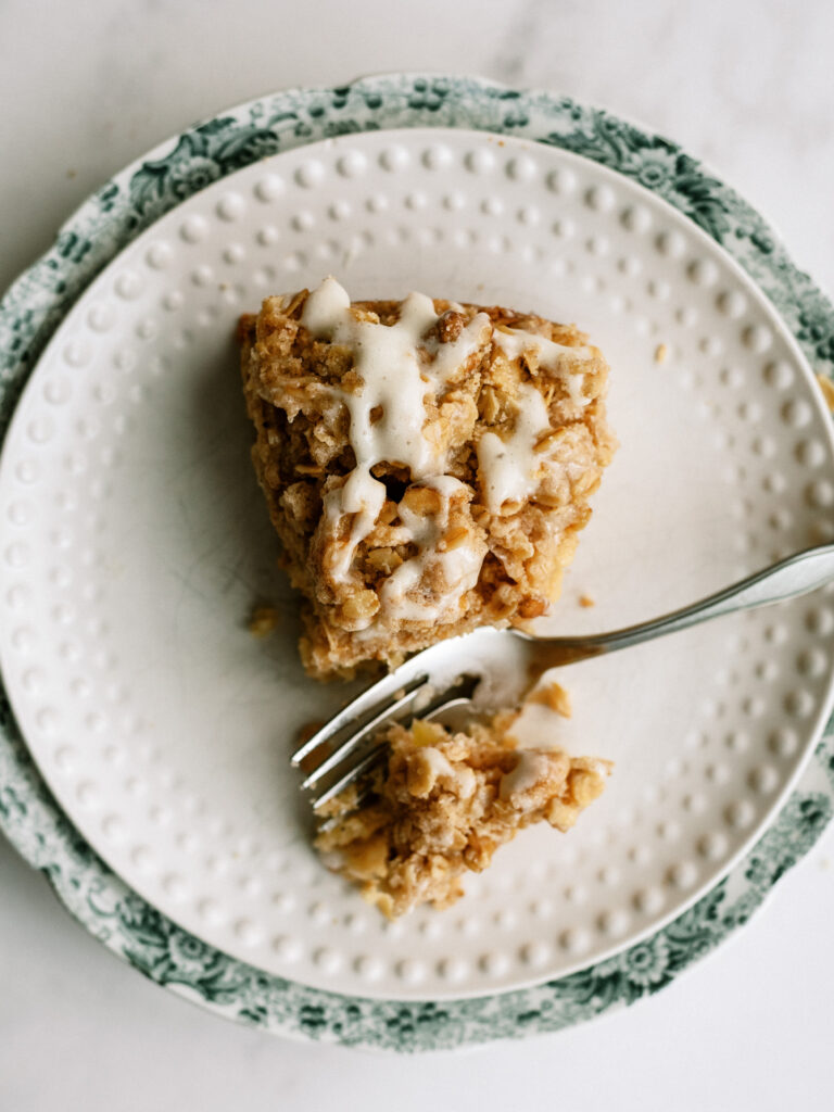 fork taking a piece out of a slice of apple cake