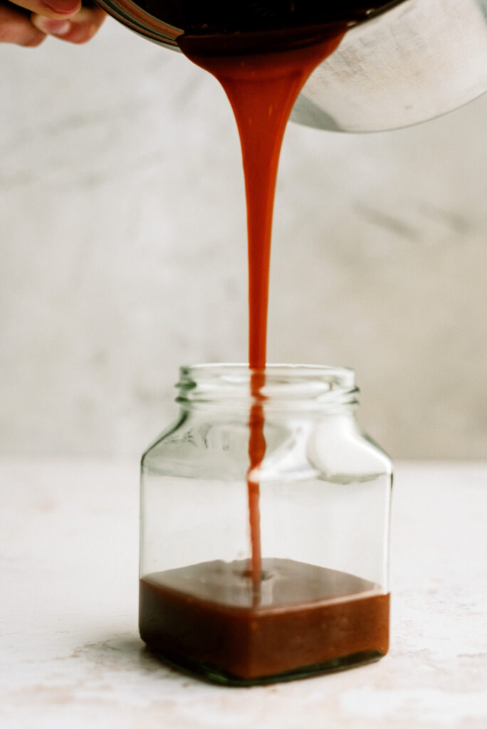 salted caramel sauce being poured into a glass jar