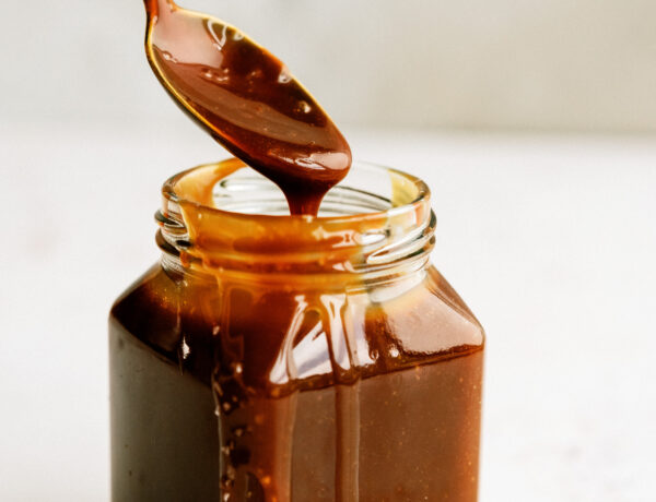 spoon exiting a jar full of salted caramel