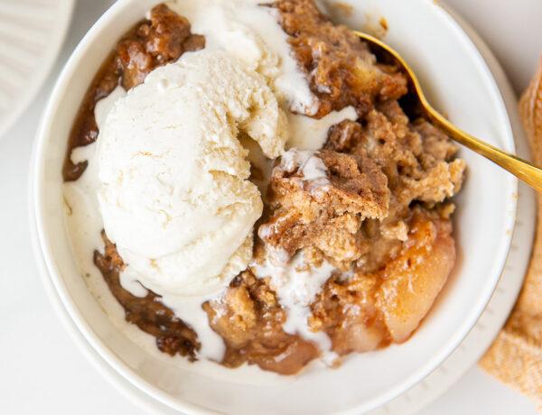 apple dump cake in a white bowl with vanilla ice cream