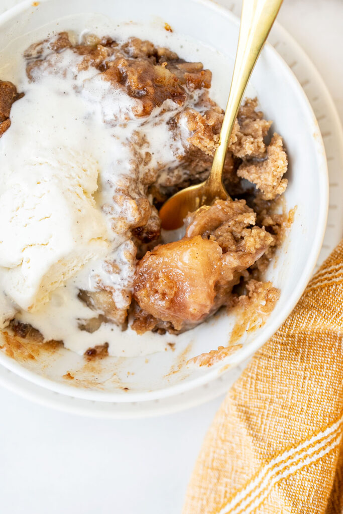 close up of apple dump cake in a white bowl with vanilla ice cream