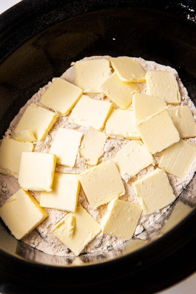slices of butter topping cake mix in a crockpot