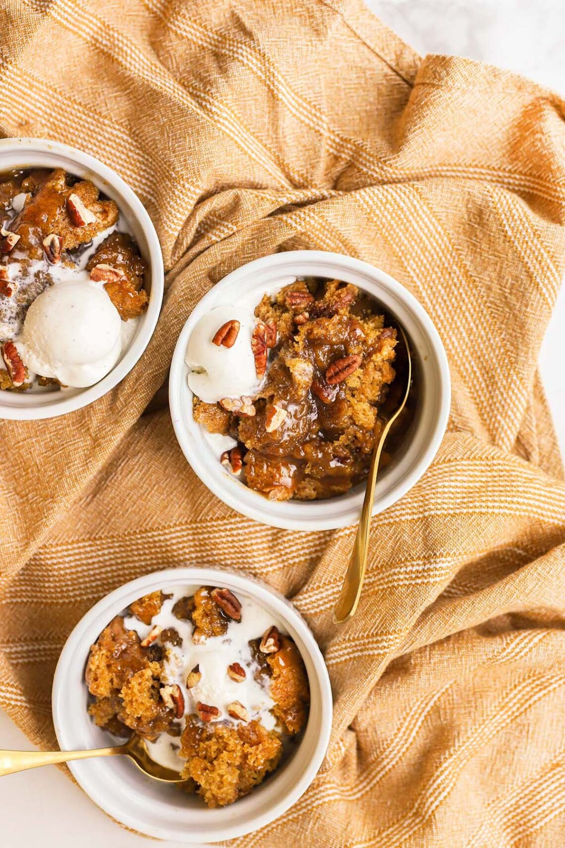 three white bowls with pumpkin cobbler and ice cream in them