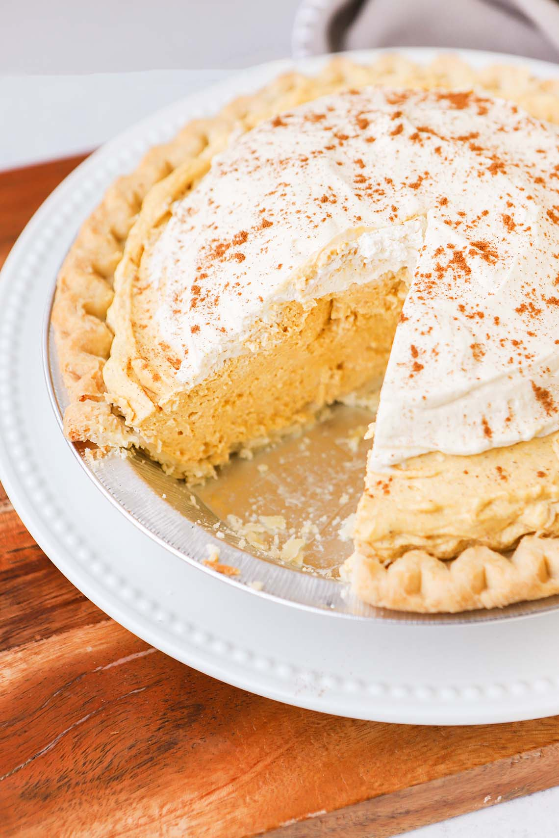 a pie plate full of pumpkin cream pie with a slice taken from it