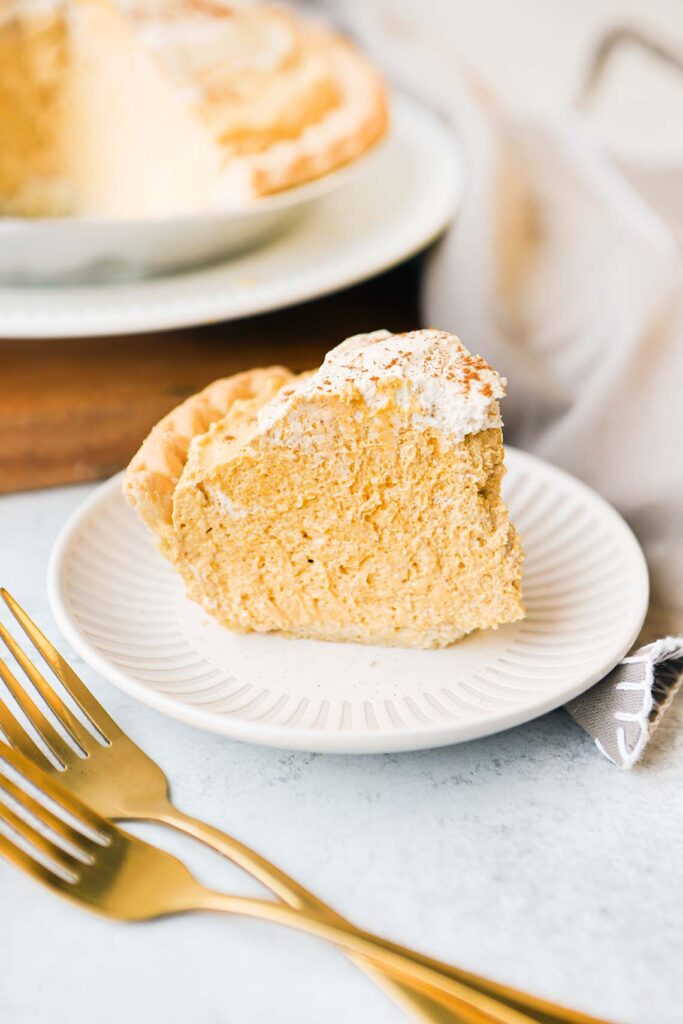 side view of a slice of pumpkin cream pie on a plate