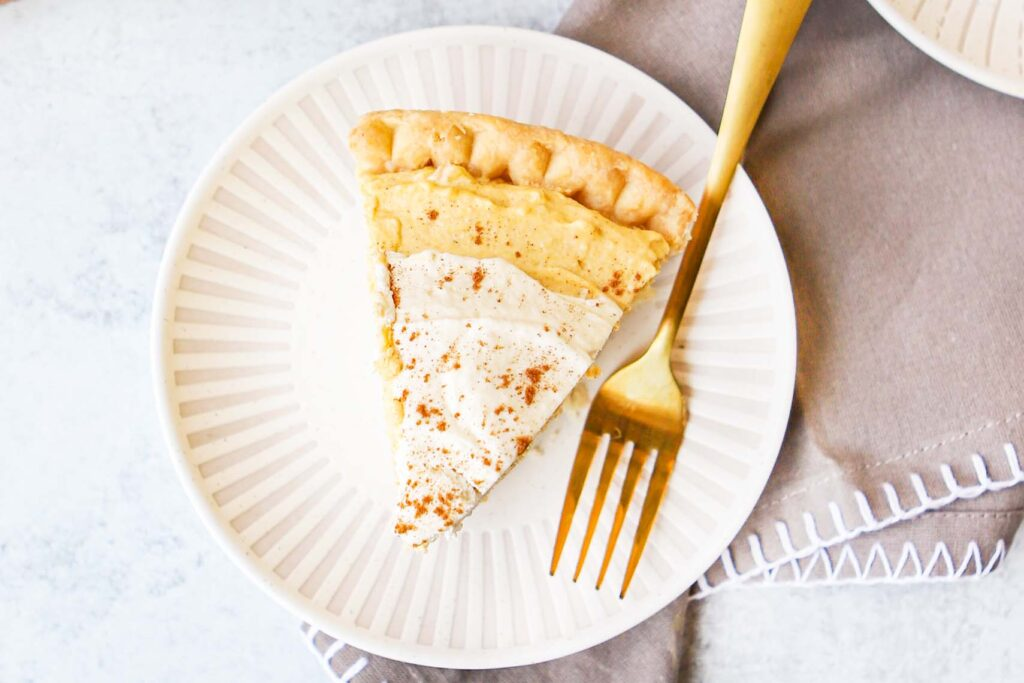 top down view of a slice of pumpkin cream pie on a plate with a fork