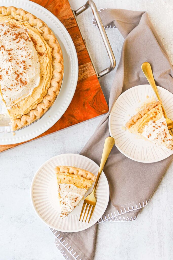 top down view of pumpkin cream pie in the corner with two plates with slices of pumpkin cream pie next to it
